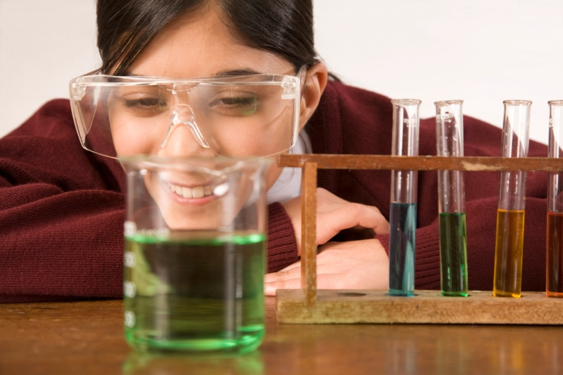 Science student watching a chemistry experiment involving a beaker and test tubes