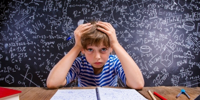 Child doing homework in front of big blackboard© iStock.com/Halfpoint.
